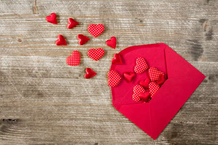 open envelope: Open envelope with red hearts on the wooden background