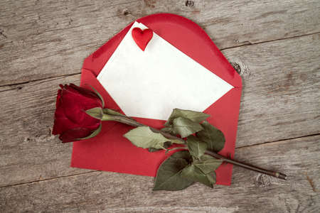 old envelope: Red envelope with blank mail and old rose  on wooden background