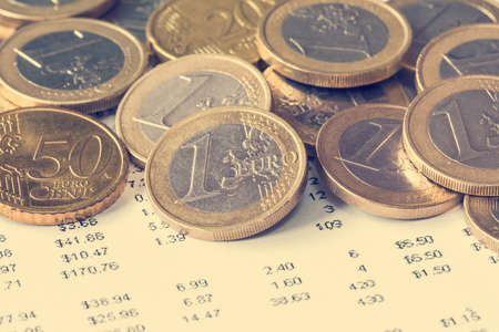 vintage document: Pile of Euro coin on financial document. Vintage color filter Stock Photo