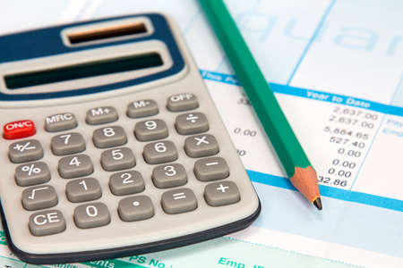 Digital calculator and pencil on the statement of payroll details Stock Photo