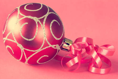 Christmas ball with ribbon on paper background