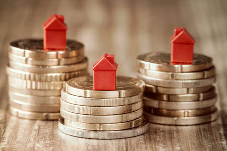 Real estate mortgage concept with small house models on top of stacked coins