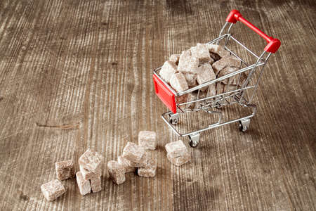 food basket: Shopping cart with brown cane sugar  on wooden background Stock Photo