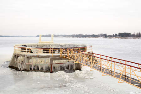 View of dam spillway in winter covered in snow and ice.