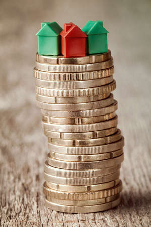 Real estate mortgage concept with small houses on top of stacked coins Stock Photo