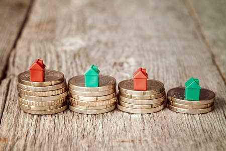Miniature plastic houses on top of stacked coins Stock Photo
