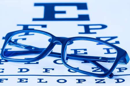 Gafas en una tabla de examen de la vista para probar la precisión de la vista. Imagen de tono azul. Foto de archivo - 73477876