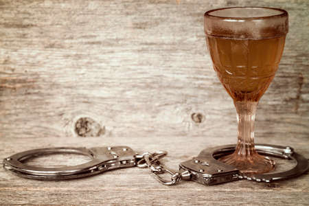 handcuffs: Glass of alcohol with handcuffs as symbol for alcohol abuse