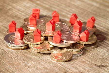 Mini houses resting on coins pile. Concept for property ladder, mortgage and real estate investment