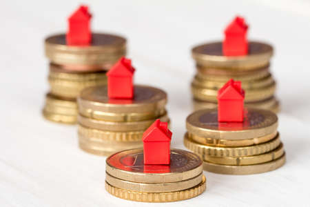 Mini houses and coins stacks. Concept for property ladder, mortgage and real estate investment