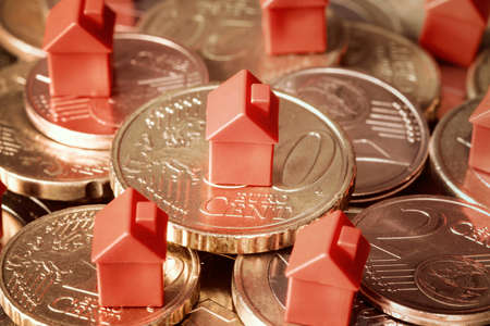 Close-up of mini houses resting on coins pile. Concept for property ladder, mortgage and real estate investment