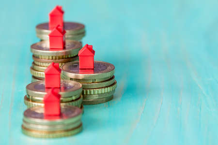 Real estate mortgage concept with small house models on coins row