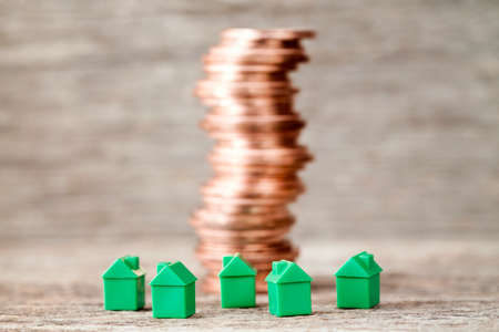 Miniature houses and copper coins stack. Concept for mortgage,property ladder and real estate investment