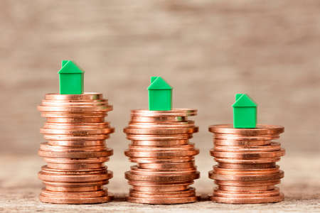 Three stacks of coins with mini houses on the top. Concept for property ladder, mortgage and real estate investment Stock Photo
