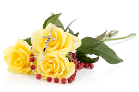 Silver crucifix and yellow roses,isolated on white background
