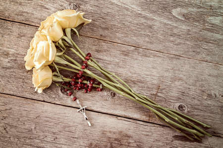Silver crucifix and yellow roses on old wooden background