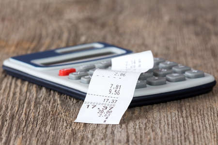 Calculator with printed receipt on wooden background Stock Photo