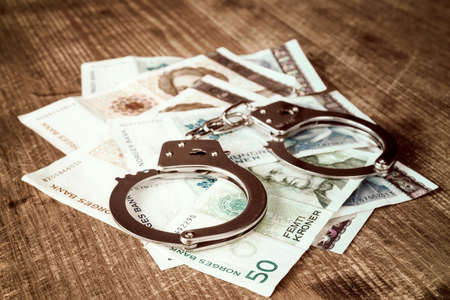 Norwegian kroner banknotes and metal handcuffs. Concept For Corruption or Fraud