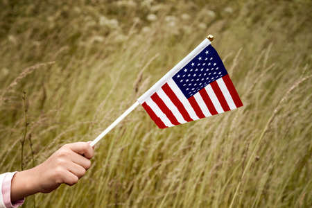 Child holding small US flag on the wind outdoor