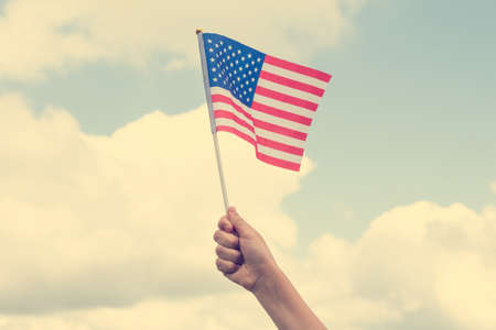 Child holding small US flag on the sky background Stock Photo