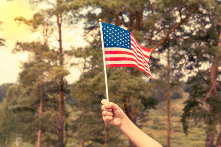 Kid holding small US flag on the wind outdoor