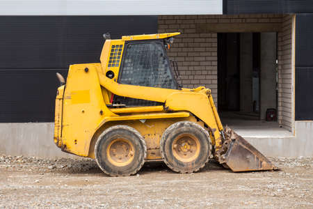 Yellow bobcat or skid loader on construction site Stock Photo