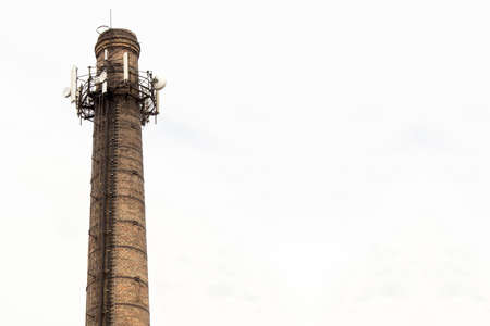 Old brick chimney with  antennas on cloudy sky background