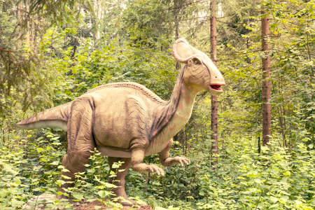 Statue of a real looking dinosaur in a green forest