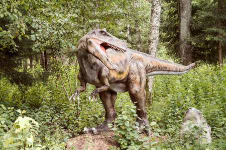 Big dinosaur model in a forest Stock Photo