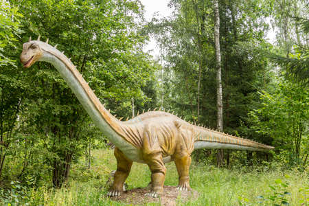 Statue of realistic dinosaur in a wild forest Stock Photo