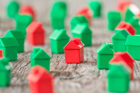 Many plastic toy houses on a wooden background.Real estate concept. Stock Photo