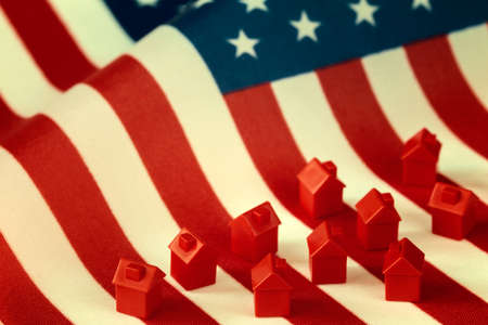 Mini houses against USA flag background. Citizenship, residence, property, real estate concept.