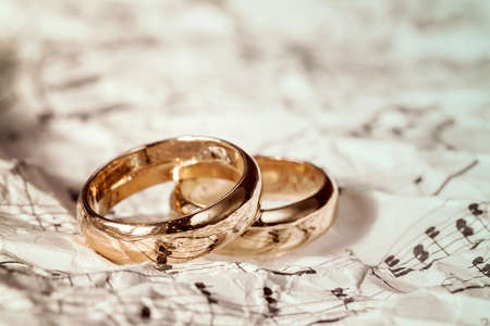 Golden wedding rings on old sheet music Stock Photo