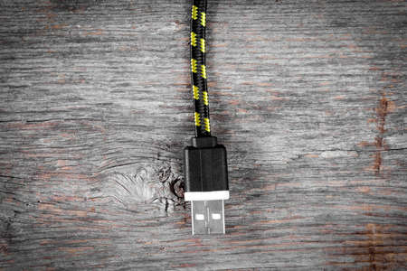 Nylon braided USB cable hanging over wooden background 版權商用圖片