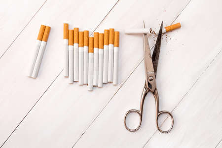 Cutting cigarettes by scissors. Anti smoking or quit smoking concept. Stock Photo