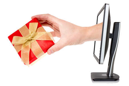 Hand with gift box comes out of monitor.Isolated on white background.