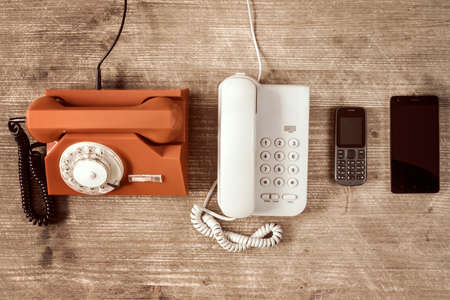 Old telephones and modern mobile phone show evolution in telecommunications