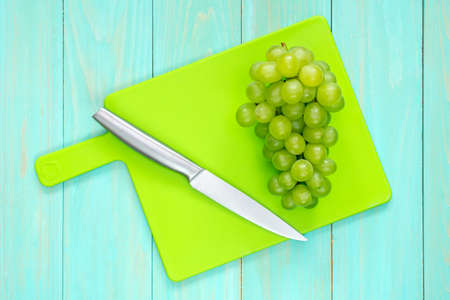 The branch of green grapes with a knife on a cutting board