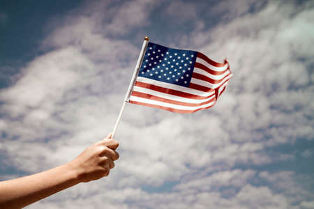 Child  waving US flag on the sky background Stock Photo