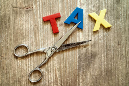 Cut of tax Concept. Scissors and the colorful plastic alphabet on wooden background. Banque d'images - 105753101