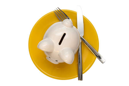 Savings consumer concept. Piggy bank on the yellow plate with fork and knife,isolated on white Stock Photo