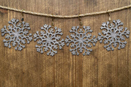 Christmas decorations (snowflakes) hanging over wooden background