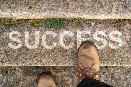 Man stepping up a stairs with word SUCCESS Stockfoto