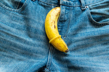 Banana in condom protruding from blue jeans 版權商用圖片