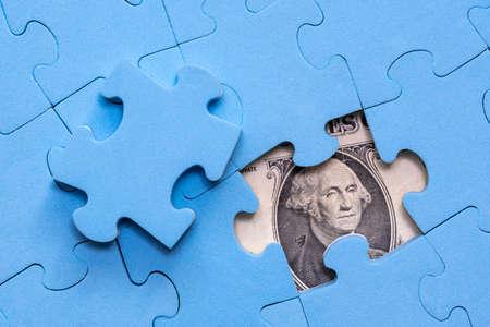 Amerikanische Dollars versteckt unter Puzzle, Geschäftskonzept der Lösung