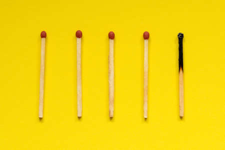 Wooden matches with one burned out on yellow background