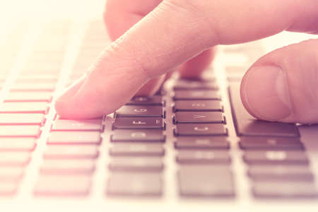 Single finger press button on laptop keyboard. Filtered image.