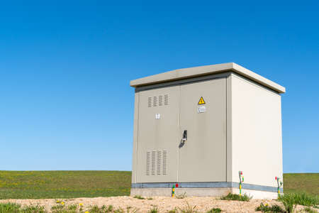 High voltage electric cabinet in park under clear blue sky
