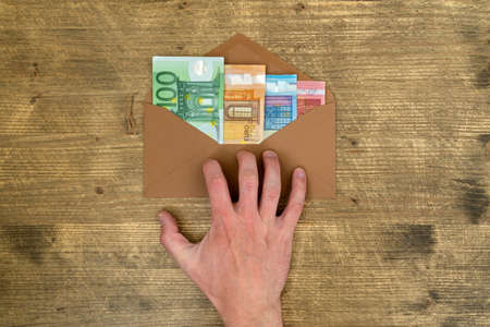Hand takes an envelope with money. Shadow economy, illegal salary in an envelope without taxes.