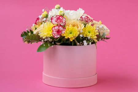 Flower arrangement in a hat box , a pot of pink for a girl on a gift